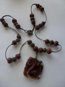 deeply carved lizard and raw ceramic beads on leather